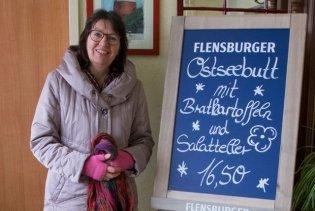Claudia vor der Angebotstafel eines Restaurants