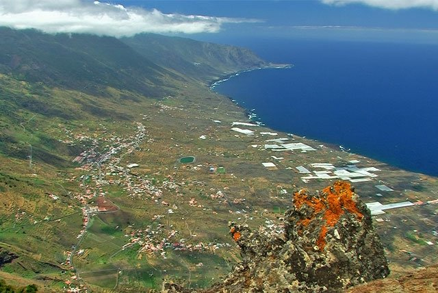 Blick in ein Tal, das links von Bergen und rechts vom Meer begrenzt wird.